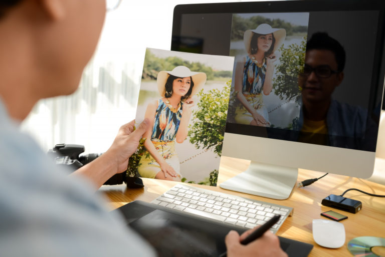 man holding a photograph of a woman and editing it on the computer